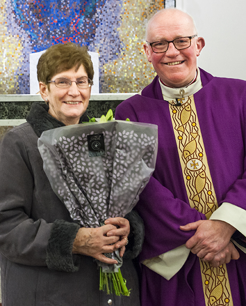 Maureen receives a bouquet of flowers from Parish Priest Canon Michael Loughlin